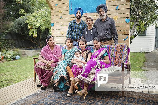 Multi-generation family posing on patio bench