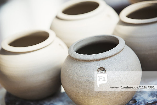 Four small round pots with round openings  vases of fresh turned clay.