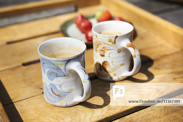 Two mugs and a plate of fruit on a garden table.