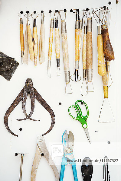 A tool board  with brushes  hand tools and pliers and curved shaing tools  calipers hanging on the wall.