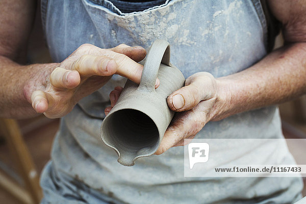 A potter handling a wet clay pot  smoothing the outside and preparing it for kiln firing.