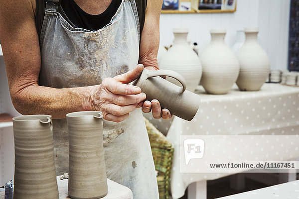 A potter handling a wet clay pot  smoothing the bottom and preparing it for kiln firing.