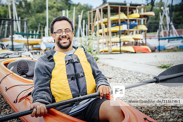Mixed Rave man sitting in kayak holding paddle