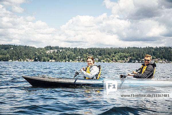 Caucasian man and woman paddling kayak