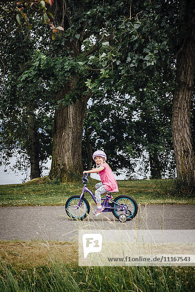 Mixed Race girl riding bicycle with training wheels