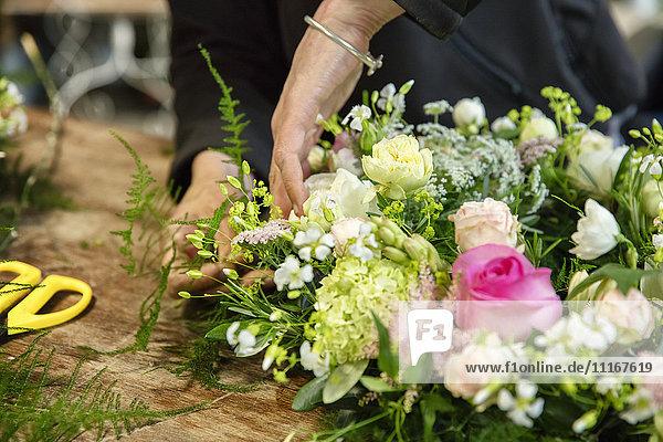 A woman working on a flower arrangement  a trained florist.