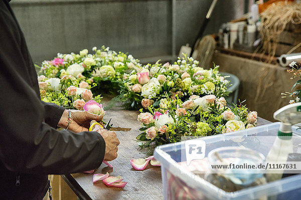 Commercial florist. A woman working on a floral decoration at a workbench.