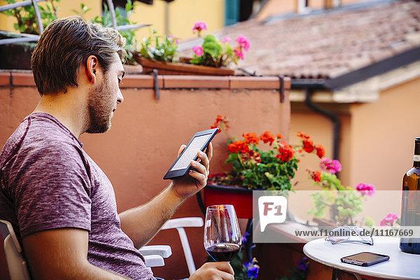 Caucasian man reading digital tablet drinking red wine