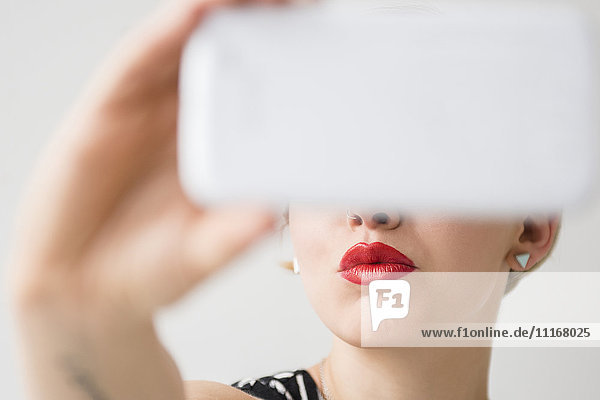 Red lips of woman posing for cell phone selfie