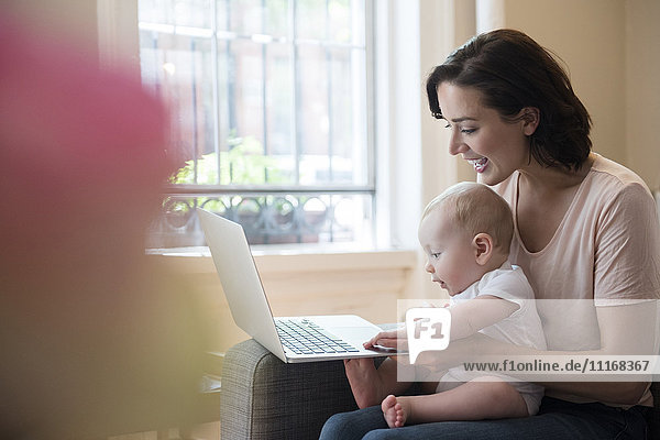 Caucasian mother holding baby in lap using laptop