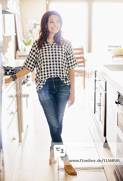Woman with long brown hair  wearing a chequered shirt  standing in a kitchen.