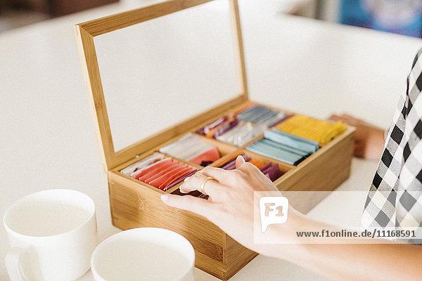 Nahaufnahme einer Frau  die in einer Küche steht  Kiste mit Teebeuteln und Tassen.