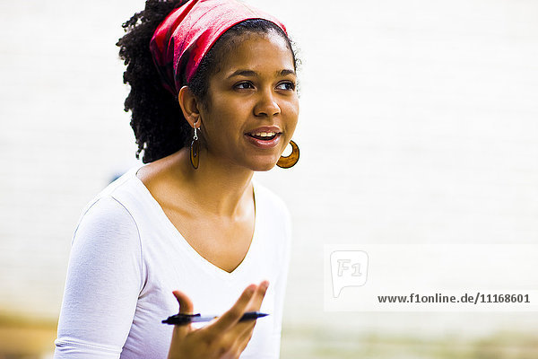 Mixed Race woman gesturing with pen