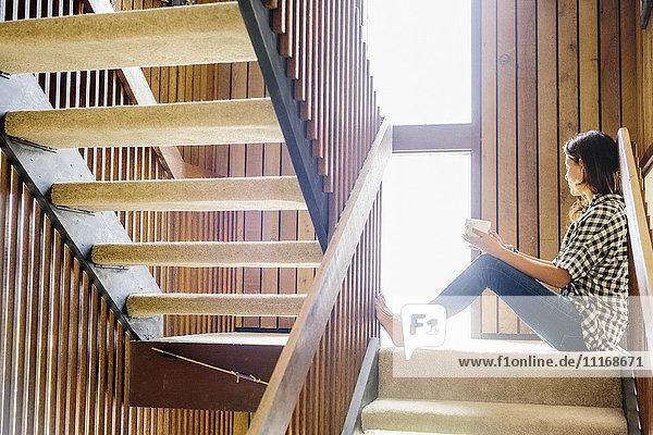 Frau mit langen braunen Haaren sitzt auf einer Holztreppe und schaut aus dem Fenster.