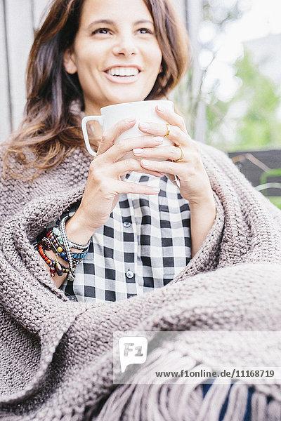 Frau mit langen braunen Haaren  in eine Decke gewickelt  einen Becher haltend.
