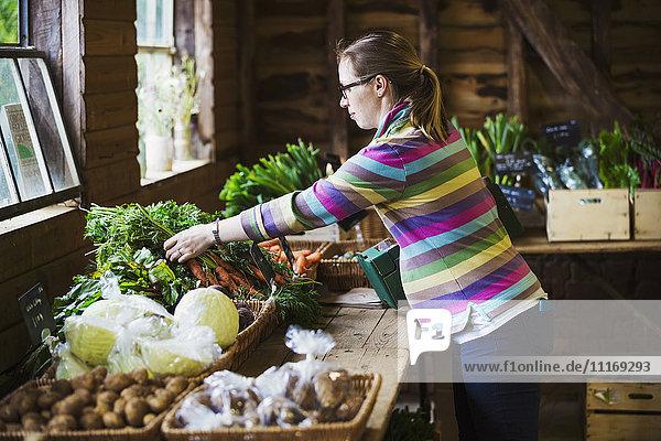 A woman handling produce in a farm shop.