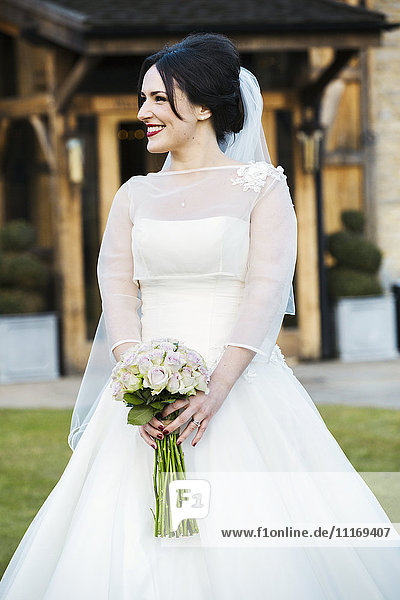 Eine Braut im Brautkleid mit einem Blumenstrauß.