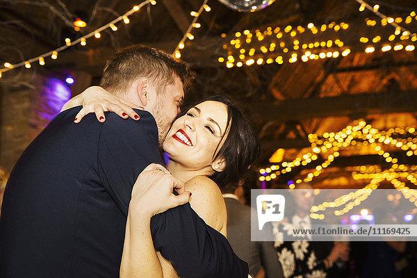 Ein frisch verheiratetes Paar  eine Braut und ein Bräutigam  die sich auf ihrer Hochzeitsfeier umarmen.