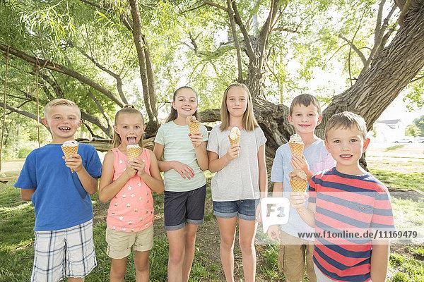 Caucasian boys and girls eating ice cream cones