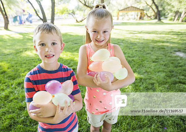 Caucasian brother and sister holding water balloons