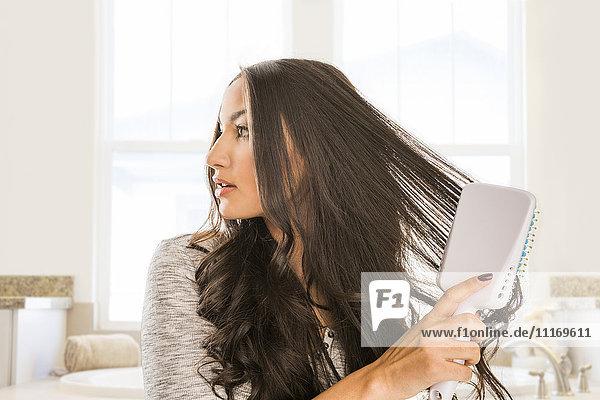 Mixed Race woman brushing hair in bathroom