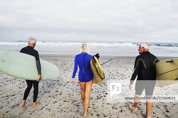 Senior woman and two senior men on a beach  wearing wetsuits and carrying surfboards.