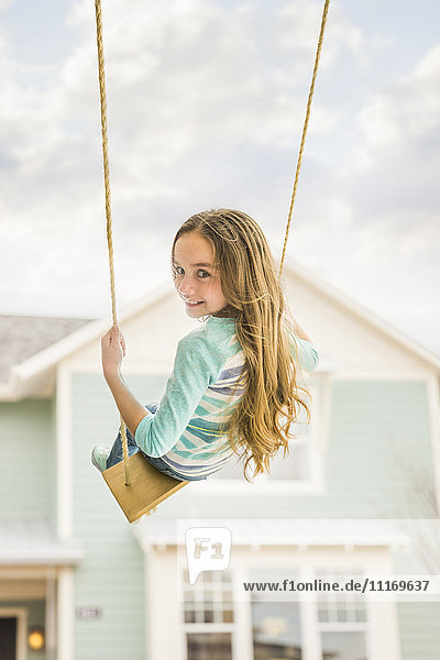 Caucasian girl on rope swing near house