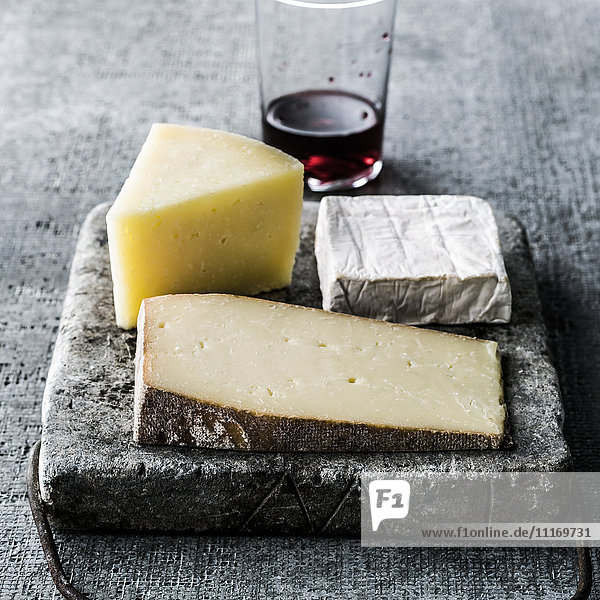 Variety of wedges of cheese on cutting board with red wine