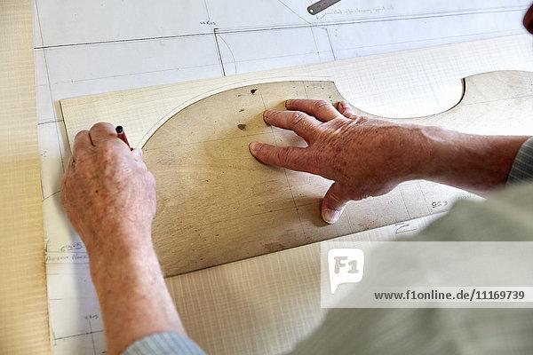 Die Werkstatt eines Geigenbauers. Geschickter Handwerker  der um den Umriss eines Holzbodens für eine Geige zeichnet. Die Werkstatt eines Geigenbauers. Geschickter Handwerker, der um den Umriss eines Holzbodens für eine Geige zeichnet.