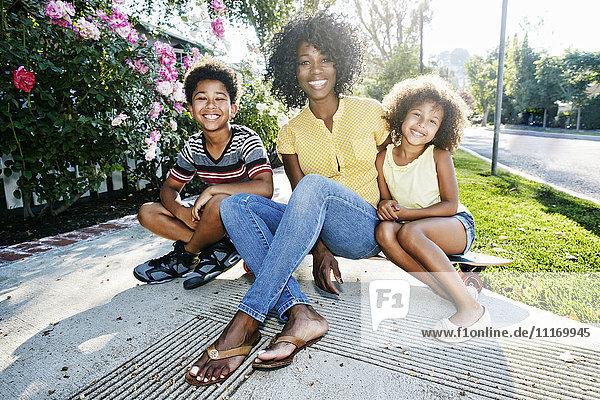 Smiling mother and children sitting on skateboard on sidewalk