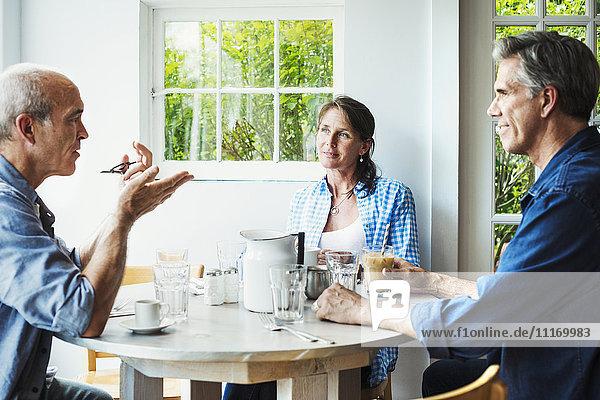 Zwei Männer und eine Frau sitzen an einem Kaffeehaustisch und unterhalten sich.