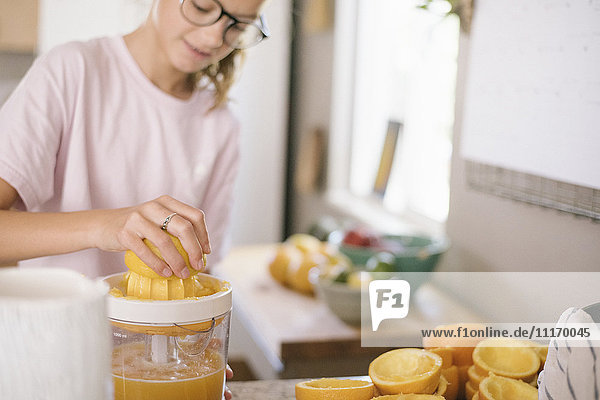 Eine Familie bereitet das Frühstück in einer Küche vor  ein Mädchen quetscht Orangen. Eine Familie bereitet das Frühstück in einer Küche vor, ein Mädchen quetscht Orangen.
