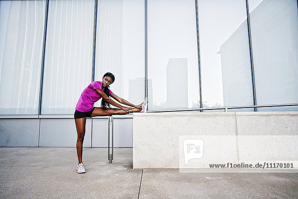 Black woman stretching leg on urban wall