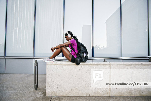 Black woman sitting on urban wall listening to headphones