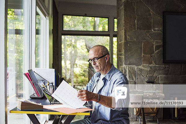 A man seated at a desk at home  working sorting through paperwork.