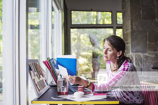 Frau  die zu Hause an einem Schreibtisch sitzt und arbeitet.