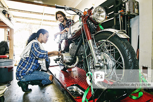 Man watching woman repairing motorcycle in garage