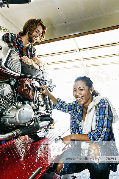 Man watching laughing woman repairing motorcycle in garage