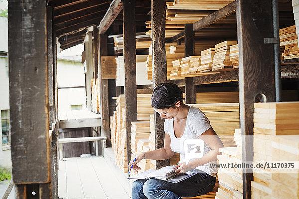 Frau  die in einem Holzlager sitzt und eine Mappe in der Hand hält.
