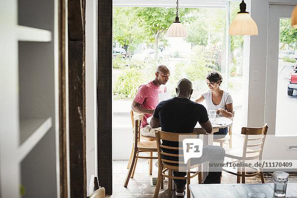 Zwei Männer und eine Frau sitzen an einem Tisch in einem Cafe und essen zu Mittag.