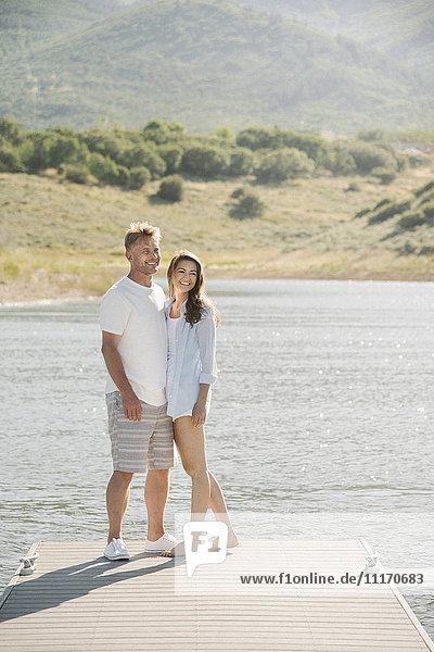 Mann und Frau stehen Seite an Seite auf einem Steg.
