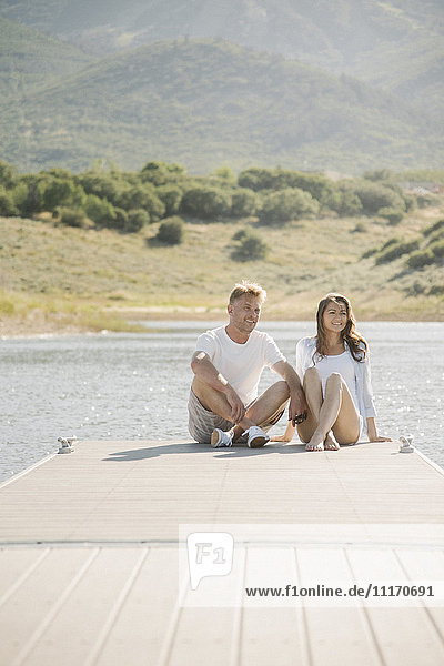 Man and woman sitting side by side on a jetty.