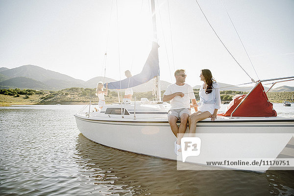 Mann und Frau sitzen auf einem Segelboot.
