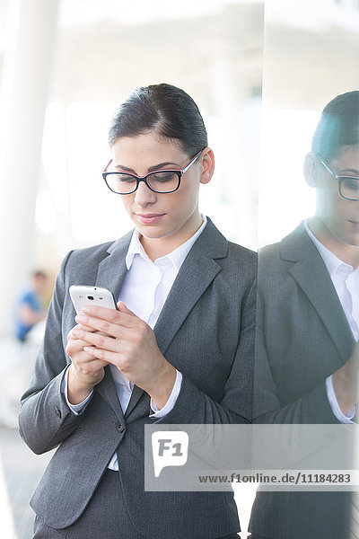 Businesswoman using cell phone while leaning on glass wall