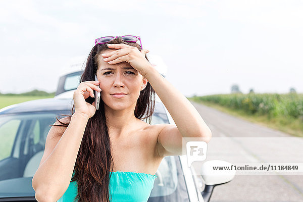 Portrait of tensed woman using cell phone against broken down car on road