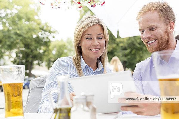 Happy businesspeople using digital tablet at sidewalk cafe