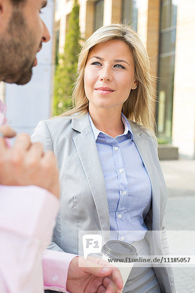Businesswoman looking at male colleague outdoors