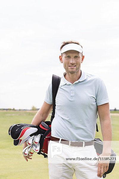 Portrait of confident man carrying golf club bag against clear sky