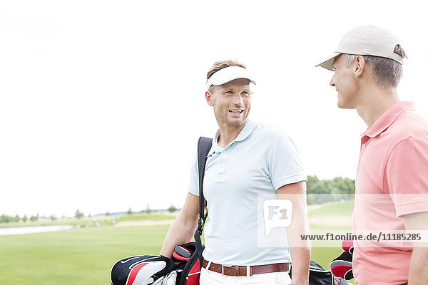 Happy golfer communicating with male friend against clear sky