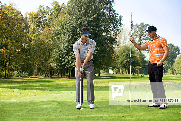 Young man with his friend playing golf in golf course